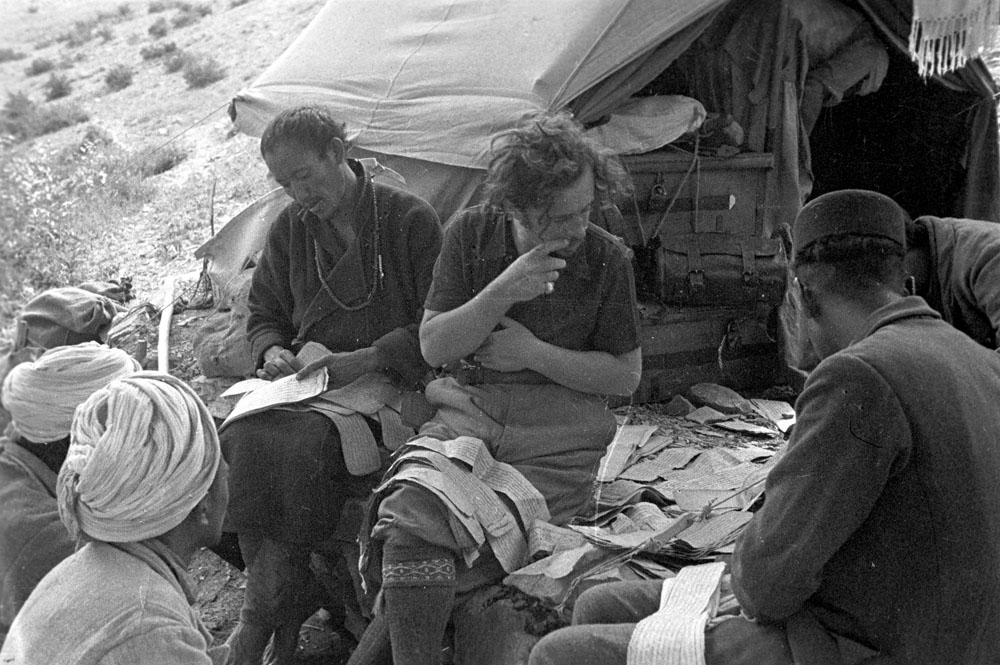 MIang (Tibet occidentale) Giuseppe Tucci riordina le pagine sciolte di libri recuperati in un deposito (1933)