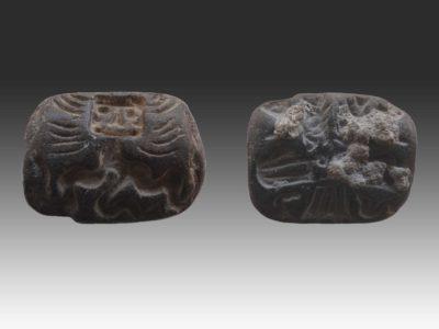 Amuleto o sigillo a stampo raffigurante su un lato una creatura dal volto umano e dal corpo serpentino, mentre sull'altro una figura femminile alata circondata da serpenti. Togolok 1, Bronzo Tardo (1950-1500 a.C.)